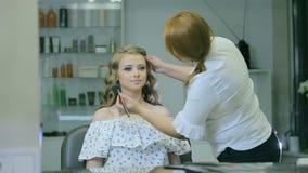 O maquilhador profissional limpa a cara da mulher com a escova cosmética filme