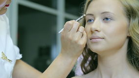 O maquilhador profissional tonifica o pastel louro do whith da sobrancelha dos modelos filme