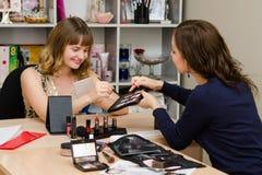 O maquilhador recomenda aquele ao escolher uma sombra para os olhos da cor da menina Fotografia de Stock Royalty Free