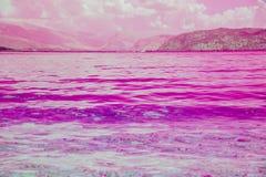 O mar abstrato do rosa da tintura da ideia, o céu, o por do sol, os mountans cor-de-rosa e o oceano roxo molham imagens de stock