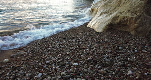 """O mar acena batendo a rocha branca em uma praia com areia, pedras e fundos Seascape do †do movimento lento dos seixos do """" filme"""