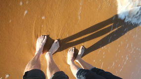 O mar acena espirrando os pés da mulher e do homem no Sandy Beach vídeos de arquivo