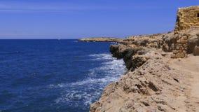 O mar acena o espirro na costa rochoso com a fortaleza no fundo do horizonte vídeos de arquivo