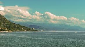 O mar ajardina… Monte e céu azul nebuloso Imagens de Stock