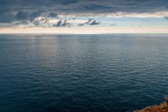 O mar azul e as nuvens de tempestade pretas, os elementos fotografia de stock royalty free
