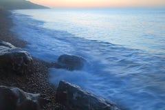 O mar borrado acena no nascer do sol Imagens de Stock