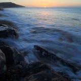 O mar borrado acena no nascer do sol Imagem de Stock