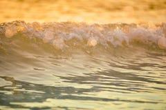 o mar da ressaca blured a onda no fundo claro dourado de da praia do por do sol Fotografia de Stock Royalty Free