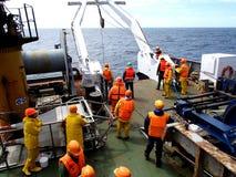 O mar de Okhotsk/Rússia - 9 de julho de 2015: Equipe da expedição da ciência na proa do equipamento de espera r do rv Akademik La imagem de stock royalty free