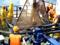 O mar de Okhotsk/Rússia - 21 de julho de 2015: Equipe da expedição da ciência na proa de rv Akademik Lavrentyev Deployme da rede  imagens de stock royalty free