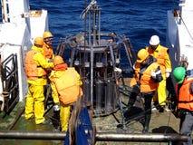 O mar de Okhotsk/Rússia - 9 de julho de 2015: Equipe da expedição da ciência na proa de rv Akademik Lavrentyev que prepara o mult imagens de stock