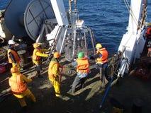 O mar de Okhotsk/Rússia - 10 de julho de 2015: Equipe da expedição da ciência na proa de rv Akademik Lavrentyev que prepara o mul imagens de stock