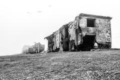 O mar destrói casas de pedra abandonadas velhas na praia fotos de stock royalty free