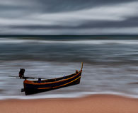 O mar e a praia atacam com barco de pesca, borrão de movimento Fotografia de Stock Royalty Free