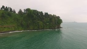 O mar encantador de turquesa acena os montes verdes de lavagem, convidando para relaxar, turismo video estoque
