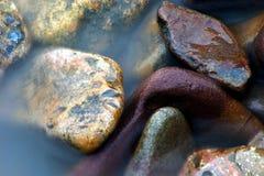 O mar encontra seixos imagens de stock