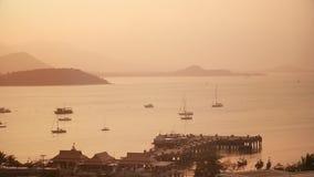 O mar envia a posição no estacionamento no porto e o por do sol da noite que reflete na água do mar video estoque