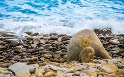 O mar frio do outono com um pulverizador das ondas cobre uma praia rochosa fotos de stock royalty free