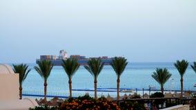 O Mar Vermelho, um grande navio de carga navega no mar, não longe da praia com palmeiras filme