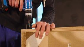 O marceneiro é mestre está apertando os parafusos em detalhes de madeira para montar vídeos de arquivo