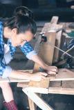 O marceneiro da mulher em uma oficina home tira em uma linha corte do lápis da placa de madeira da serra Imagem de Stock Royalty Free