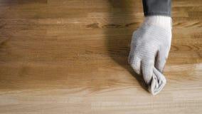 O marceneiro está cobrindo a placa de madeira grande pela composição protetora, usando a parte de tela, close-up das mãos filme