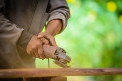 O marceneiro trabalha com um purificador bonde e uns produtos de madeira dos processos Fotografia de Stock