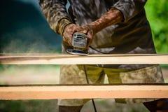 O marceneiro trabalha com um purificador bonde e uns produtos de madeira dos processos Imagem de Stock Royalty Free