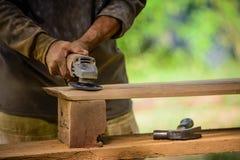 O marceneiro trabalha com um purificador bonde e uns produtos de madeira dos processos Fotografia de Stock Royalty Free