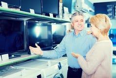 O marido e a esposa alegres escolhem para se a tevê no centro de Imagens de Stock Royalty Free