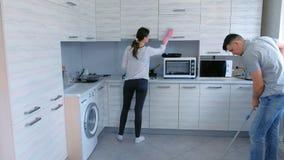 O marido e a esposa estão limpando na cozinha junto O homem lava o assoalho com um espanador e a mulher limpa a mobília