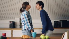 O marido e a esposa felizes do casal estão dançando na cozinha da casa acolhedor apreciação que abraça, do riso e do beijo filme