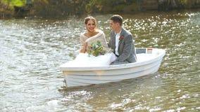 O marido e a esposa felizes estão sentando-se em um barco e estão rindo-se de sua vida alegre vídeos de arquivo