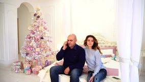 O marido e a esposa felizes usam o smartphone para felicitar parentes nos feriados, sentando-se na cama no quarto com festivo vídeos de arquivo