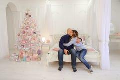 O marido e a esposa felizes usam o smartphone para felicitar parentes fotos de stock royalty free