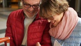 O marido e a esposa s?o rir, olhando fotos no smartphone Retrato pr?ximo de um par maduro feliz video estoque