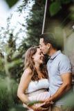 O marido está beijando sua esposa grávida em sua testa fotos de stock