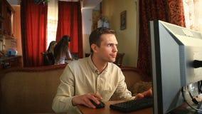 O marido joga jogos de computador, e suas esposa e crianças são ocupadas na cozinha Sua dependência do Internet do ` s do marido vídeos de arquivo