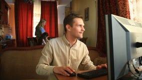 O marido joga jogos de computador, e suas esposa e crianças são ocupadas na cozinha Sua dependência do Internet do ` s do marido video estoque