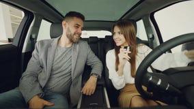 O marido loving está dando a chave do carro a sua esposa feliz ao sentar-se dentro do automóvel novo com interior e de couro agra vídeos de arquivo