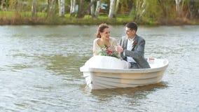 O marido satisfeito diz estórias boas a sua esposa nova em um barco no mar aberto video estoque