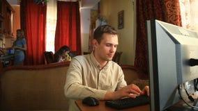 O marido senta-se no computador em redes sociais, quando suas esposa e crianças forem ocupadas na cozinha o marido tem vídeos de arquivo