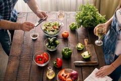 O marido toma imagens de como sua esposa está preparando o jantar Imagens de Stock Royalty Free
