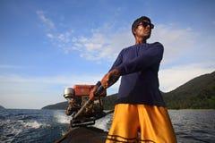O marinheiro não identificado controla o leme do barco da cauda longa Imagens de Stock