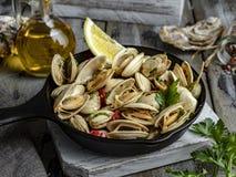 O marisco cozinhado cozinhou moluscos na parcela da bandeja do ferro com limão e tempero fotografia de stock royalty free