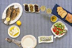 O marisco recentemente cozinhado grelhou peixes do sargo, sardinhas no azeite e salada do vegetal, azeitonas, queijo de feta, pão fotografia de stock