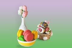 O marshmallow doce colorido do bolinho de amêndoa da Páscoa floresce em um vaso branco, ovos coloridos em uma cesta em um fundo c imagens de stock