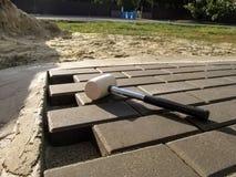 O martelo de borracha encontra-se na superfície de um ` cinzento uncompleted dos tijolos do ` do pavimento fotografia de stock