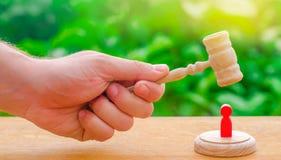 O martelo do ` s do juiz pairou sobre a figura humana vermelha Conceito de justiça e do litígio A decisão do destino do réu imagens de stock