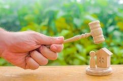 O martelo dos juizes pairou sobre a figura de madeira e humana Conceito de justiça e do litígio A decisão do destino do defe fotos de stock